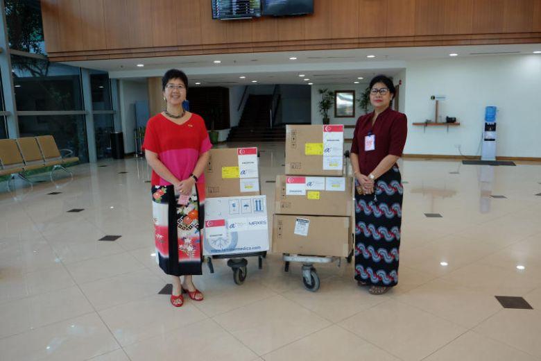 Đại sứ Singapore tại Myanmar - Vanessa Chan (trái) bàn giao các vật tư y tế tài trợ của Singapore cho Giám đốc Phòng thí nghiệm Y tế Quốc gia Myanmar - Htay Htay Tin, bao gồm 3.000 bộ xét nghiệm chẩn đoán và hai máy phản ứng chuỗi Polymerase (PCR)